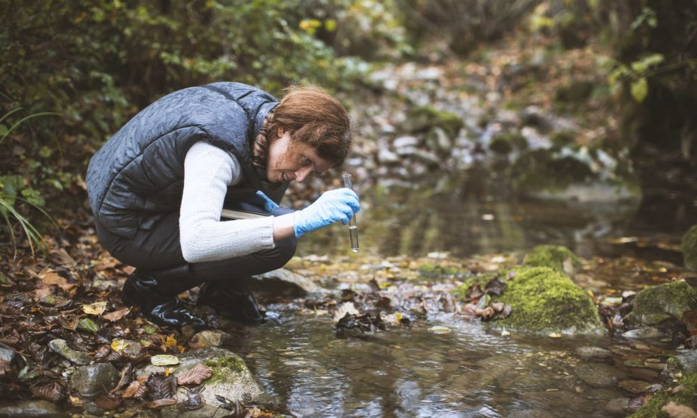 Woman Biological Researcher Taking a Water Sample from a stream.