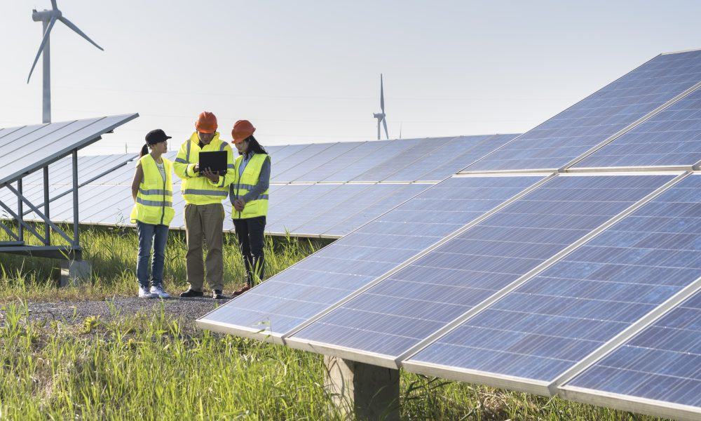 workers at a renewable energy plan, young asian engineers working in solar power station.